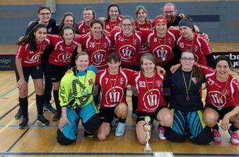 Teamfoto der SG Berlin Floorball Spielerinnen mit Pokal und Silbermedaillen.