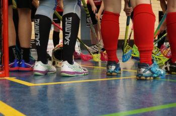 SportlerInnen scheinen in einem Kreis zu sehen. Fuße bis Knie in Spotrbekleidung sind fotografiert. In der Mitte treffen die Floorball-Schläger der SpielerInnen.